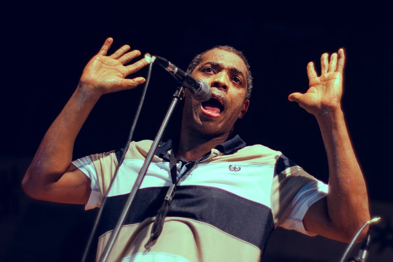 Femi Kuti at mic, hands in air